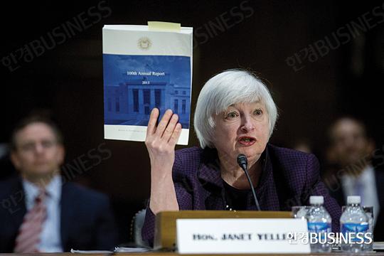 재닛 옐런 미국 중앙은행(Fed) 의장이 2월 24일 열린 미국 상원 통화정책 청문회에서 미국 경제와 금리 인상 시기 등에 대해 설명하며 Fed의 연간 보고서를 들어 보이고 있다.