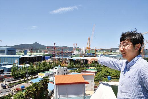 양승훈 경남대 교수가 대우조선해양 옥포조선소 북문 인근의 원룸 옥상에서 조선소 방향을 가리키고 있다.