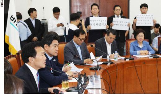 손학규(왼쪽) 바른미래당 대표가 국회에서 7월 19일 열린 최고위원회의에서 당 혁신을 요구하는 혁신위원들이 피켓을 들고 시위하는 가운데 발언하고 있다. /연합뉴스