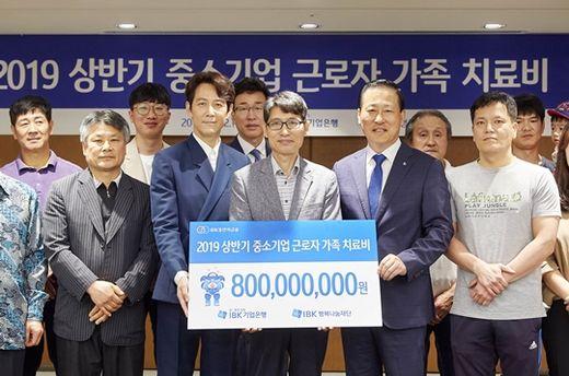 (사진) 김도진(앞줄 오른쪽 둘째) IBK기업은행장이 중소기업 노동자 가족들에게 치료비를 전달한 후 기념 촬영을 하고 있다. /IBK기업은행 제공