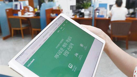 최근 IT와 금융의 융합으로 새로운 금융서비스가 선보이고 있다. 핀테크 활성화를 위해 금융규제 개선이 필요하다는 요구가 높아지고 있다. 사진은 서울 중구의 한 은행에서 핀테크 서비스를 이용하는 모습을 연출한 모습./ 한국경제신문