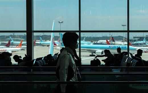 (사진) 국내·국제선 항공기 탑승객 마스크 착용 의무화 시행 첫날인 5월 27일 인천공항 제2여객터미널에서 마스크를 쓴 공항 관계자가 지나가고 있다. /한국경제신문